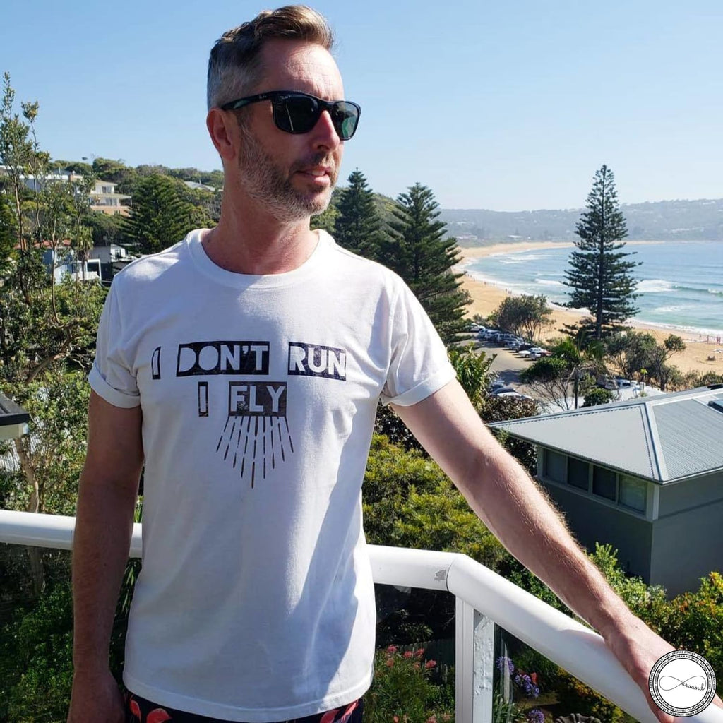 Male model wearing Around Eco fair trade and ecofriendly white graphic tee with the words I Don't Run I Fly Travel tshirt