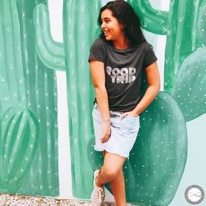 Female model wearing custom made Around Eco fair trade and ecofriendly dark gray graphic tee with the words Roadtrip tshirt