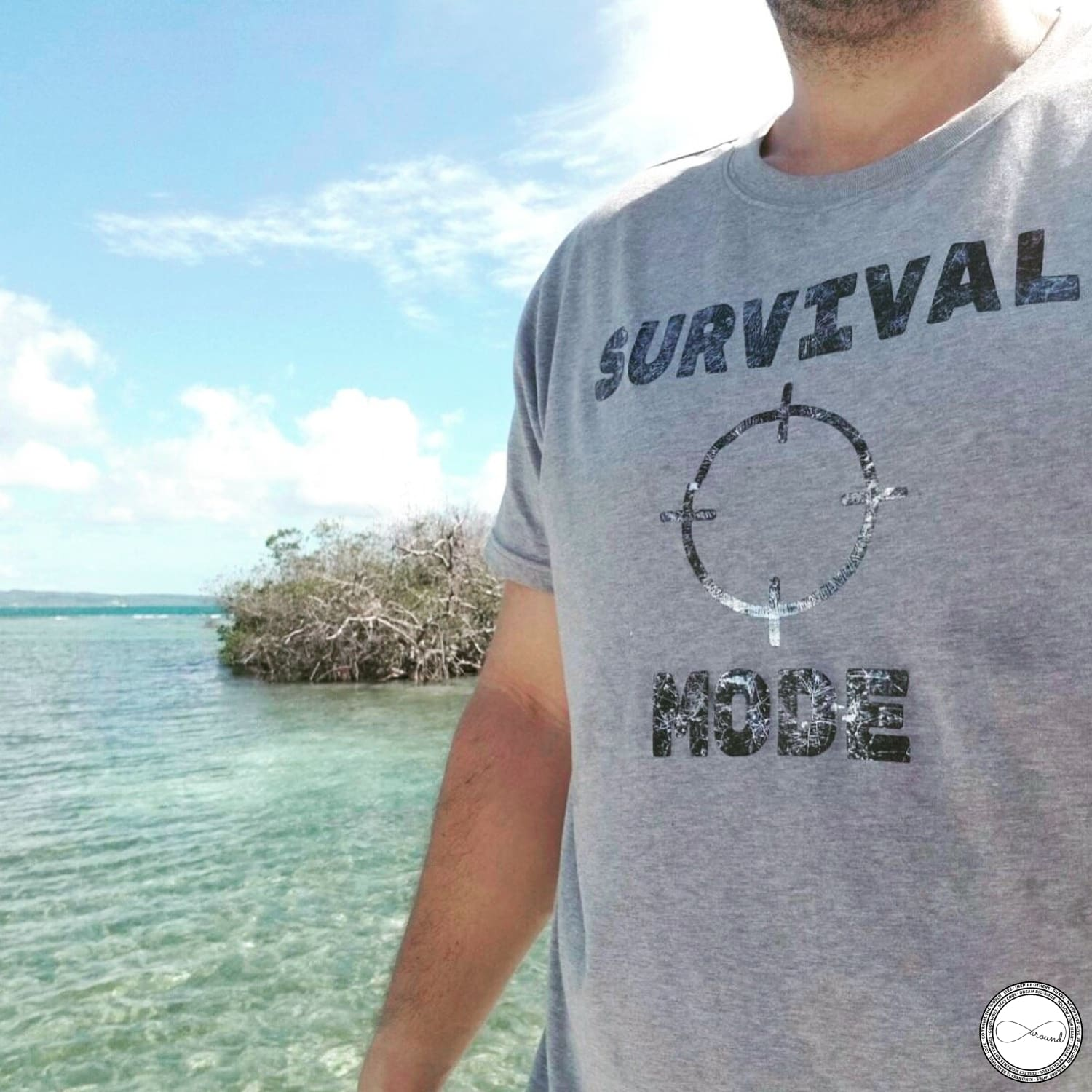 Male model wearing custom made Around Eco fair trade and ecofriendly light gray graphic tee with the words Survival Mode Travel tshirt
