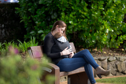 Mother sitting on a park bench wearing her baby in a Peek-a-Baby wrap carrier