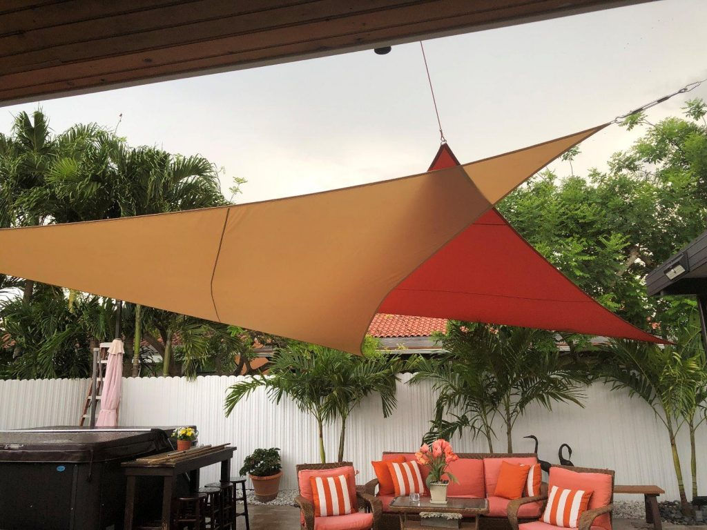 two triangular shade sails cover an  outdoor patio