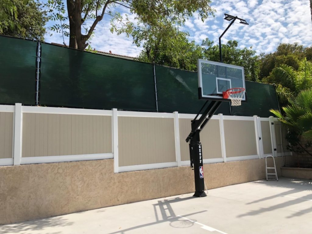 basketball court with a tall privacy screen fence