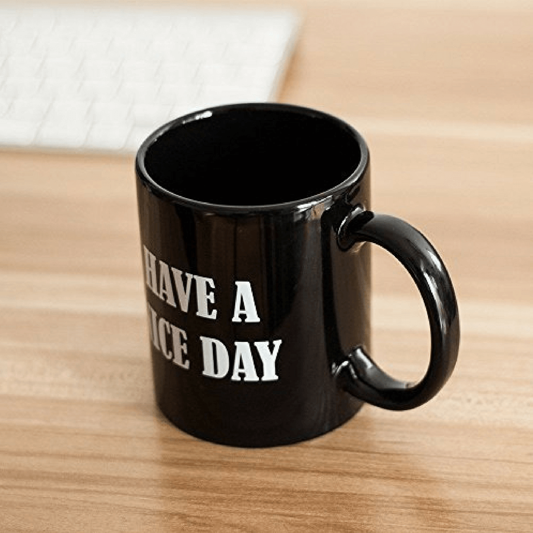 Black coffee mug that says have a nice day with middle finger in the bottom. Black mug with wooden desktop and white keyboard. Glossy black coffee cup.