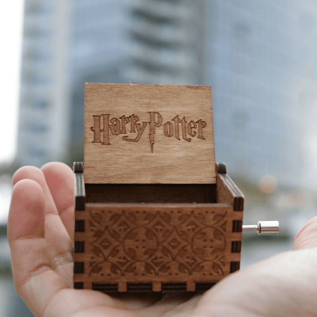 Wooden harry potter music box on the palm of a hand.