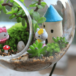 Castle with plants inside of a glass terrarium.