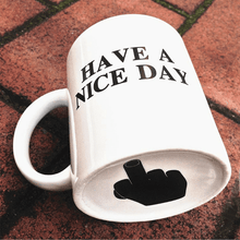 Load image into Gallery viewer, White mug that says have a nice day with middle finger in the bottom. White have a nice day cup with handle.