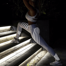 Model lunging wearing glowing led pants at night.
