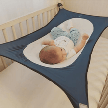 Infant resting on the portable newborn bed.