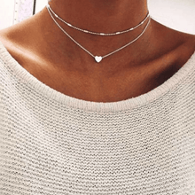 Model wearing layered love necklaces on neck.