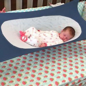 Baby sleeping on the portable newborn bed.