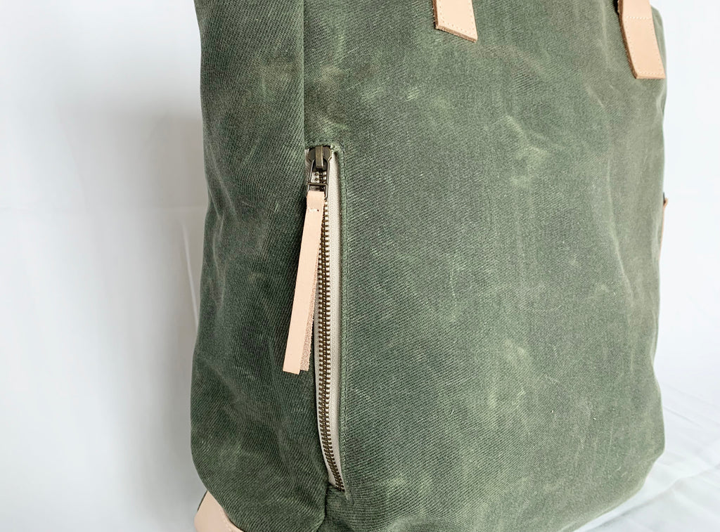 The Wild One, the olive tote, with a view of the clean lined exterior zipper pocket.