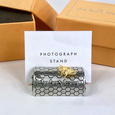 "Featuring a golden honeybee and embossed with the phrase, ""the bees knees,"" these photo stands would be a thoughtful graduation or bridal party gift. What an easy way to keep those favorite mementos close at hand!  Cast in 100% lead-free fine pewter Made in Vermont Beautifully gift boxed"