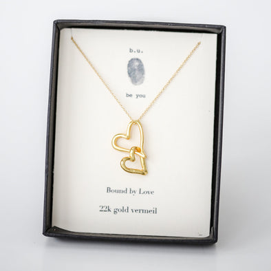 """Bound by Love"" handmade gold and silver necklace features two beautiful interlocking hearts.  925 Silver with 22k gold vermeil Artisan-Made Beautifully Boxed for giving Adjustable chain length: 16"" extends to 18"""