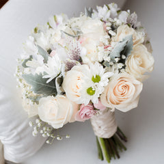 White roses and daisies in a bouquet tied with twine