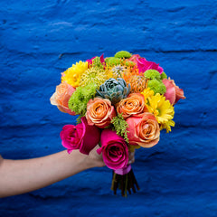 Orange roses, pink roses, and yellow daisies in a bouquet being held in front of a blue wall