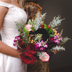 Bridal bouquet with black succulents and red roses being held by a bride with a white dress
