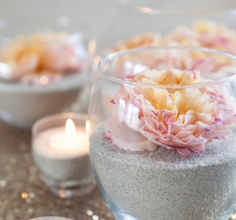 Clear glass cup with wedding flower centerpiece in sand