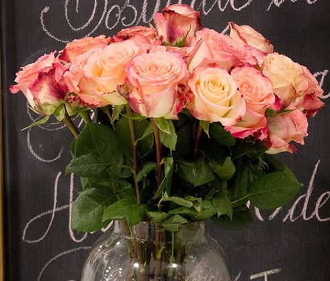 A vase filled with light pink and cream roses