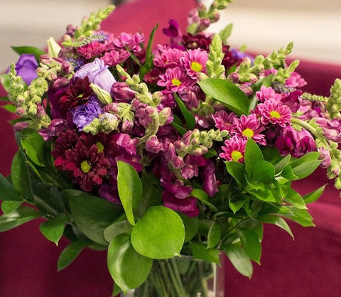 A bouquet of green and maroon flowers