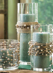 3 clear vases with green candles inside them and twine with pearls wrapped around