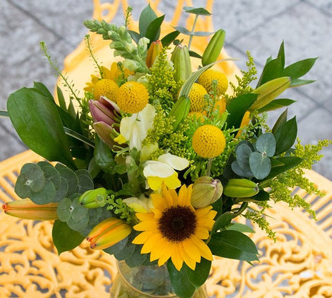 A vase willed with yellow daisies and poms