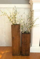 Two wooden vases, one tall and one short with plants in them