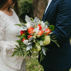 Orange rose bouquet being held by a bride and groom