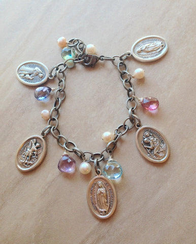 Silver tone religious charm bracelet with topaz and pearls.