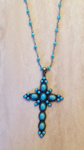 Turquoise studded cross necklace.