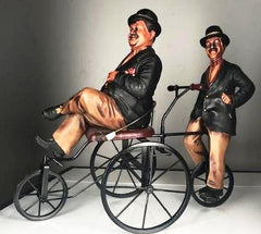 "Laurel and Hardy on a metal 4 wheeled bicycle built for two. It stands about 18"" high and is 22"" long."