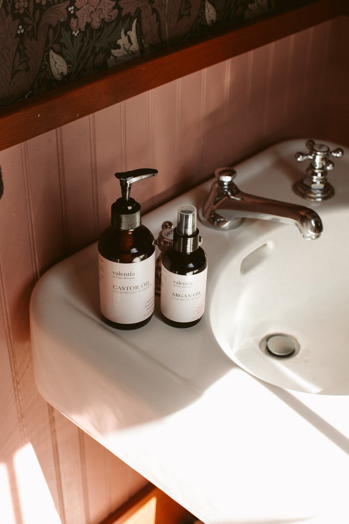 Amber bottle of organic castor oil and argan oil on bathroom sink