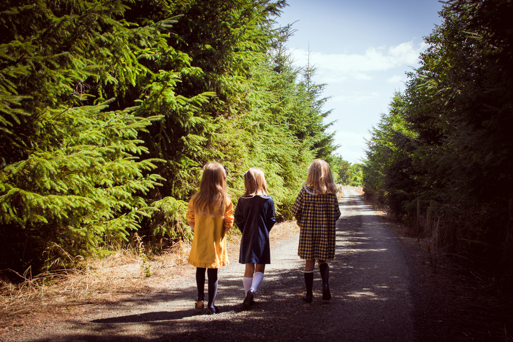 three girls walking in the forest