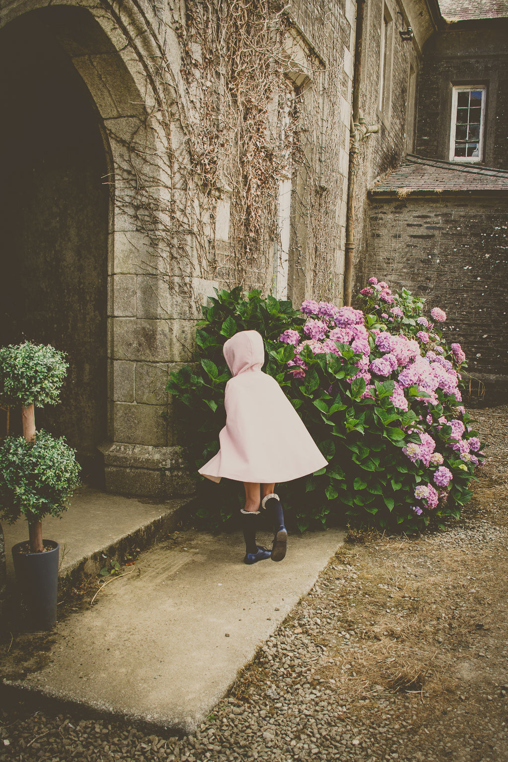 little girl wearing pink cape in a whimsical setting