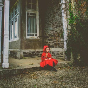 lityle girl wearing red cape sitting on the step of an old house