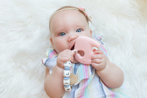 baby chewing on pink elephant teether toy and pacifier clip