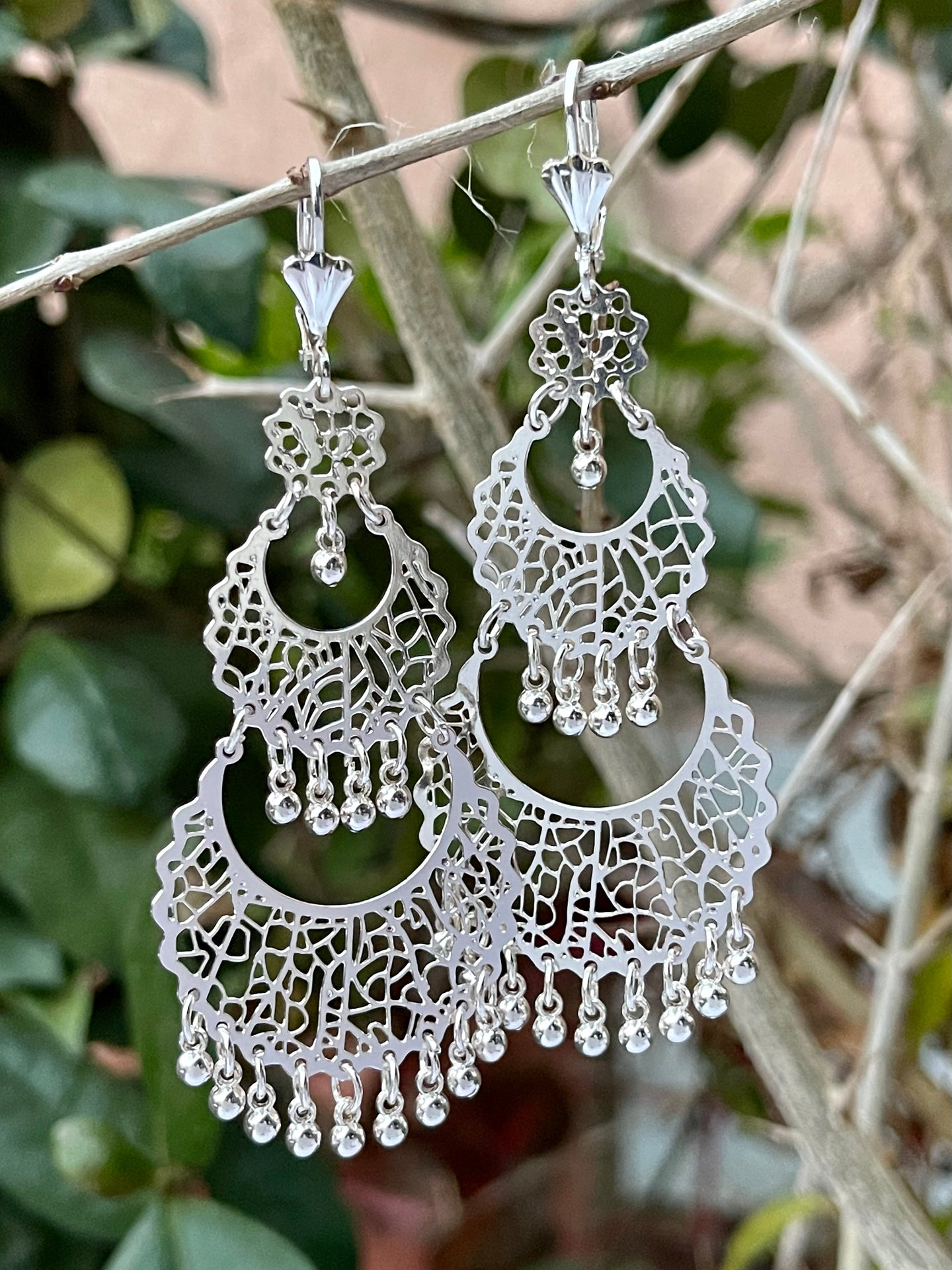 Abstract design chandelier style  dangle earrings in 14k white gold plating.