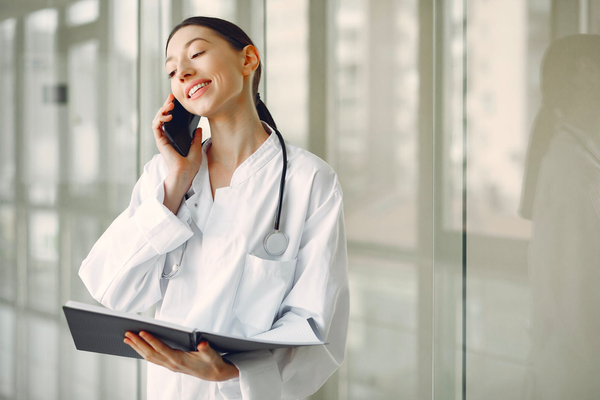 Female doctor talking on the phone and holding a folder - Hormonal Imbalance in Women