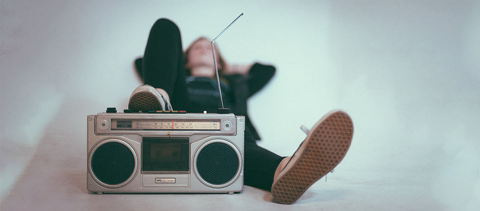 person lying down next to boombox
