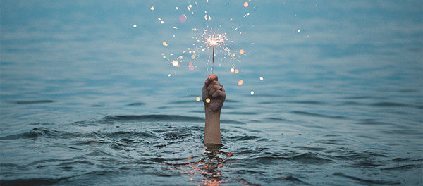 hand with body underwater, holding up a sparkler