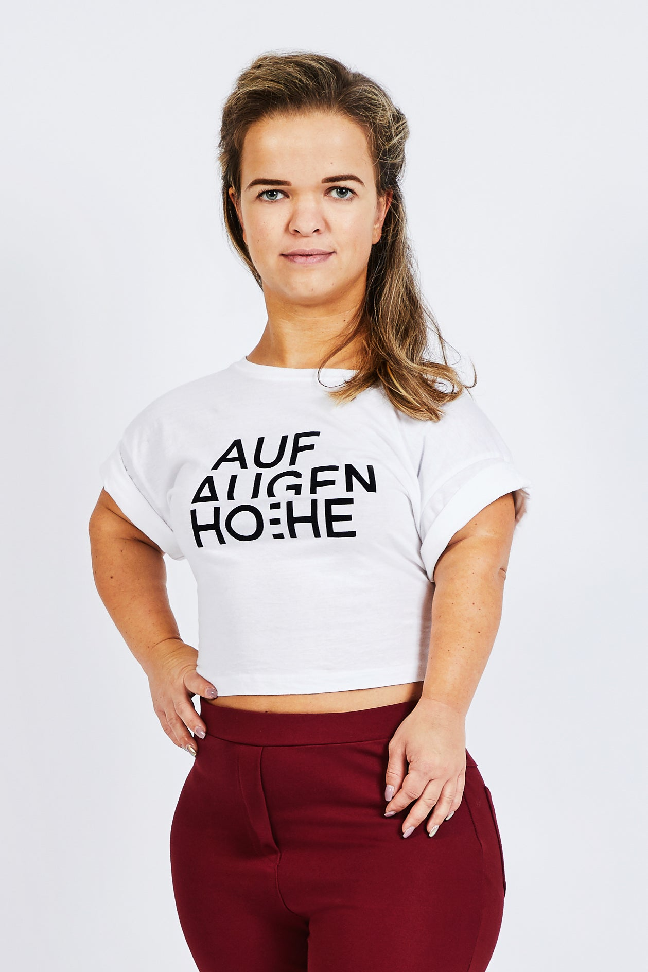 woman with dwarfism wearing white cropped top with big brand logo