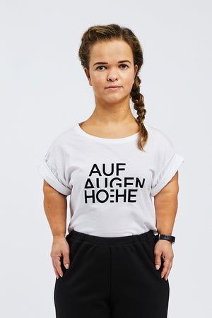 woman with dwarfism wearing white t-shirt with black brand logo