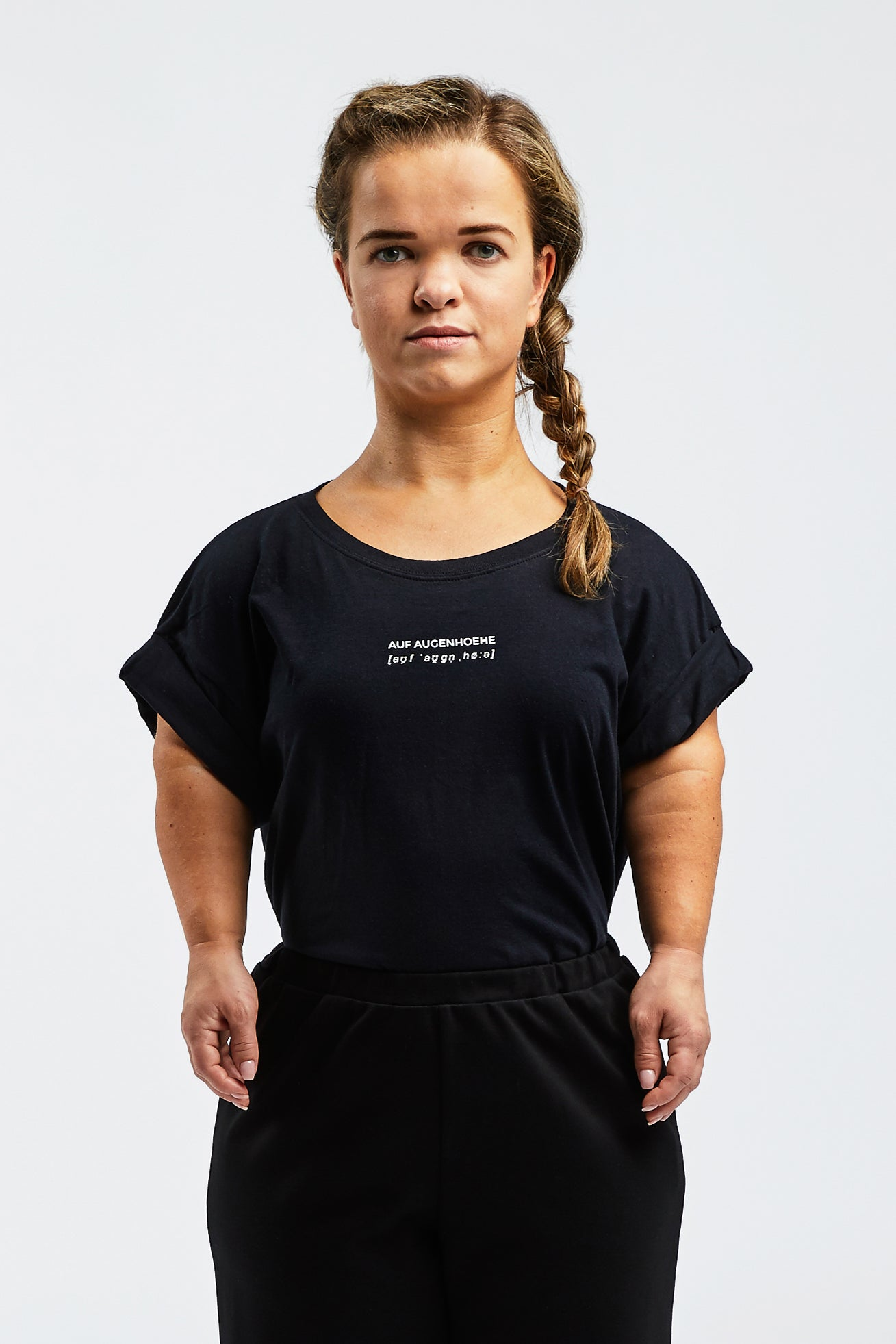 woman with dwarfism wearing a black t-shirt with small white text
