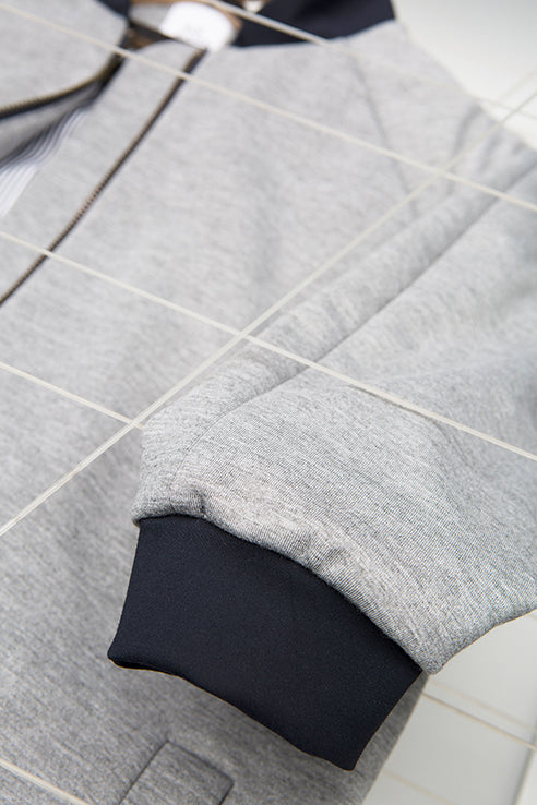 detailed view for blue sleeve on grey college jacket for people with dwarfism