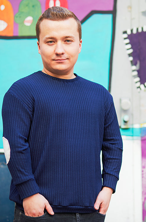 man with dwarfism wearing blue pullover