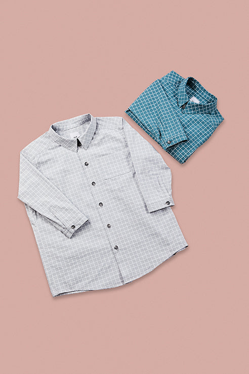 grid patterned grey shirt and folded up grid pattern blue shirt on rose background