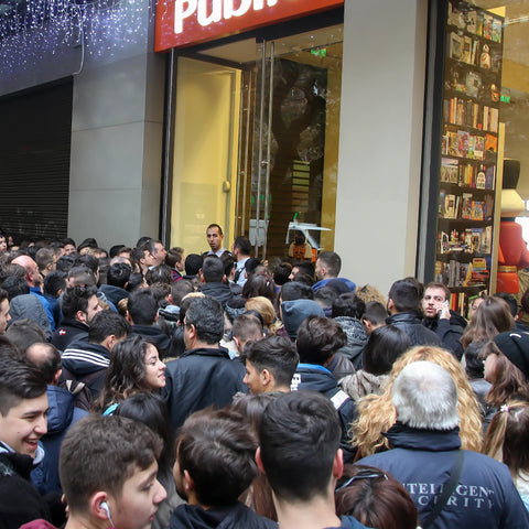 Large crowd outside a shop front