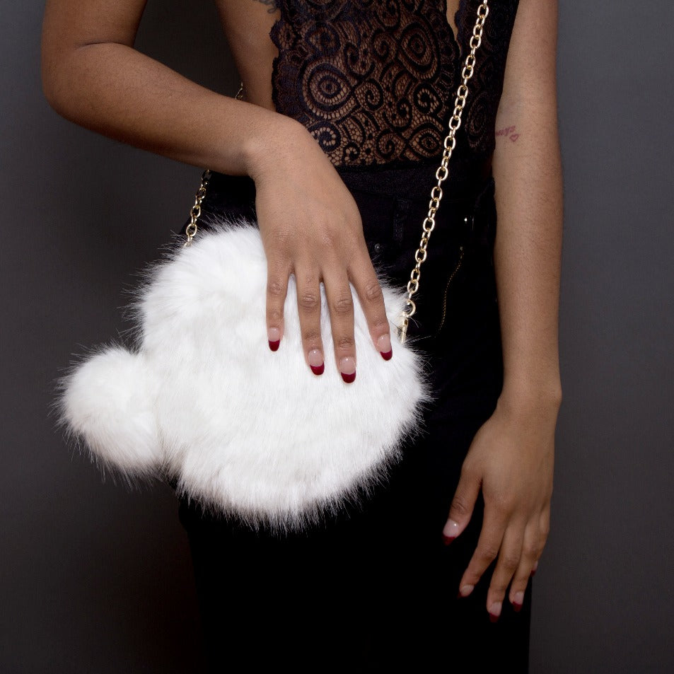 white furry purse with pom pom