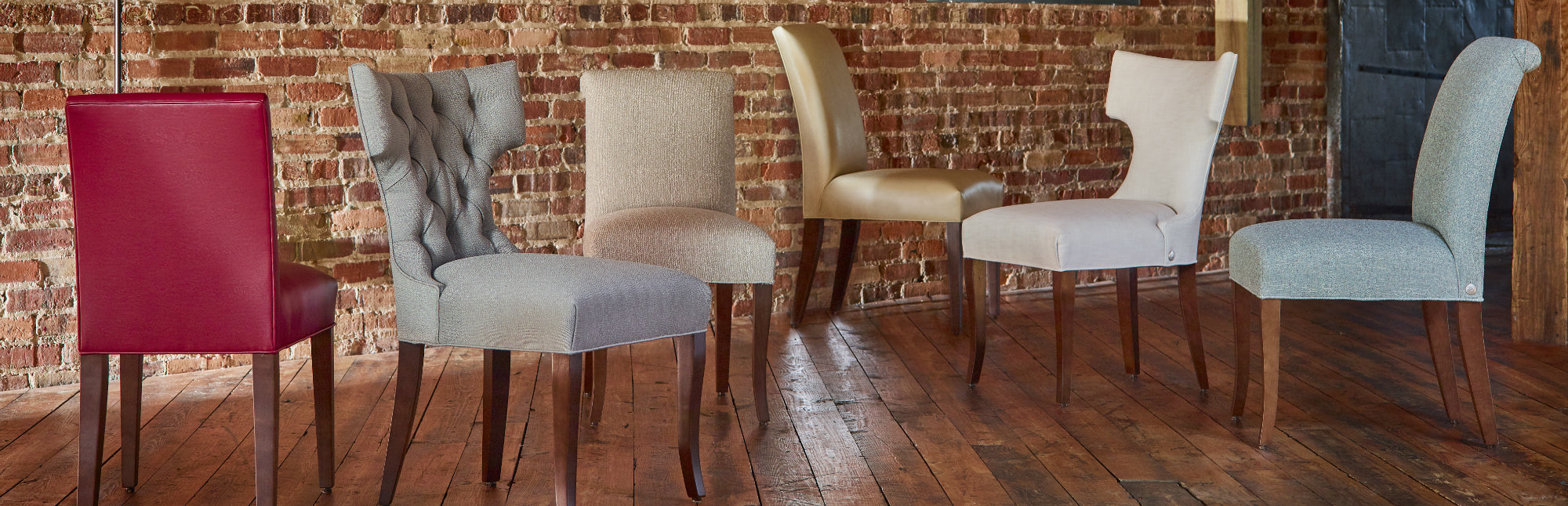 The Cudo Dining Chair collection, lined up against a brick wall.