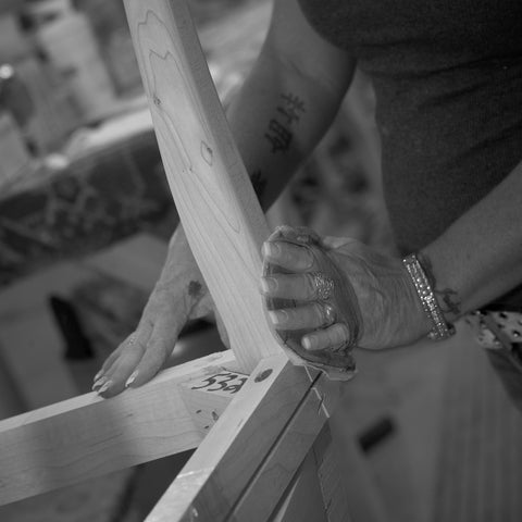 A Cudo Dining Chair frame being sanded on the plant floor in USA