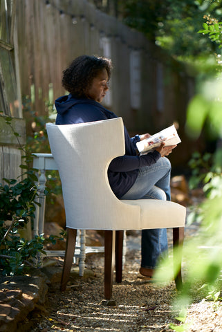 girl reading in a garden, sitting in Cudo's Cinnamon Dining Chair